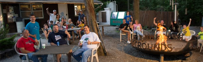 Camper's enjoying themselves in front of the campfire at Rip Van Winkle Campgrounds