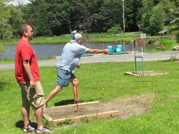 Two men playing a game of horseshoes at Rip Van Winkle Campgrounds