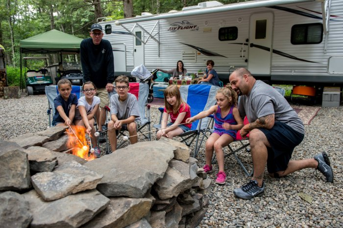 Family gathered at campfire at Rip Van Winkle Campgrounds located in the Catskills NY