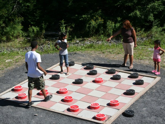 Kids playing on top of a giant checker board