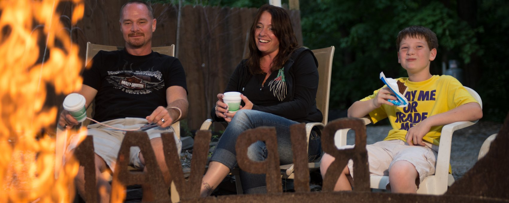 Family sitting around campfire at Rip Van Winkle Campgrounds