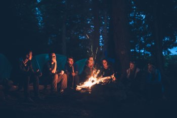 group of campers gathered around the fire at Rip Van Winkle Campgrounds in the Catskills NY