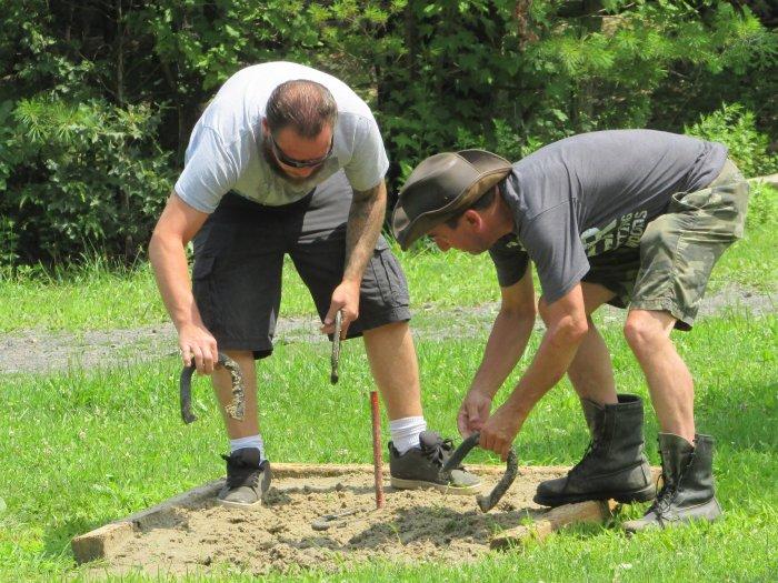2 men measuring horseshoe distances